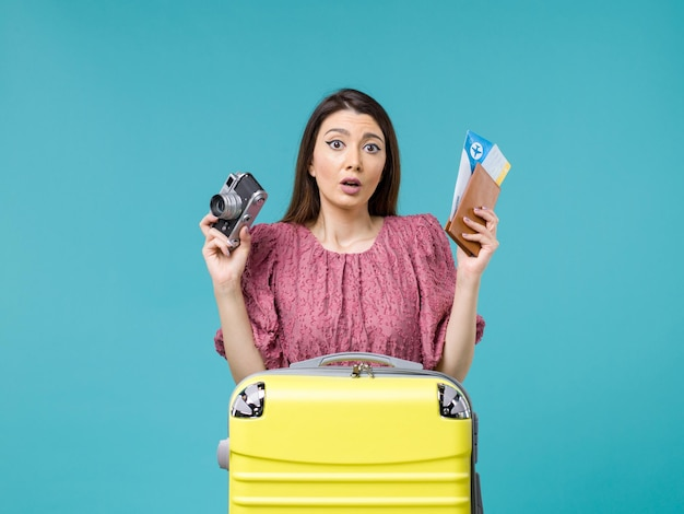 Front view young woman going in vacation holding camera and tickets on light-blue background journey vacation woman sea abroad