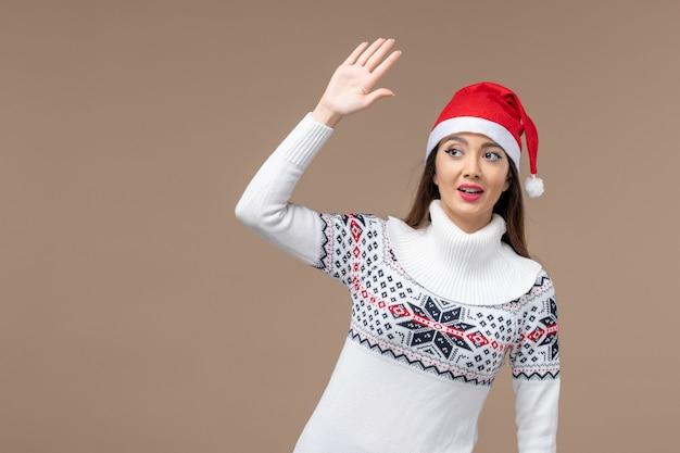 인사말 및 갈색 배경 감정 새 해 크리스마스에 흔들며 전면보기 젊은 여자