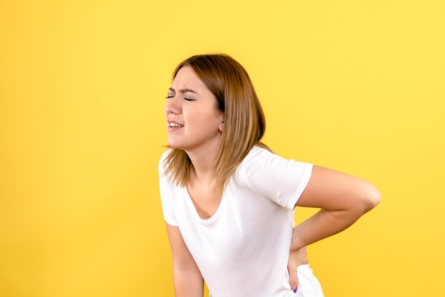 Vista frontale della giovane donna che ha mal di schiena sulla parete gialla