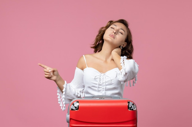 Vista frontale della giovane donna che ha mal di collo con borsa da vacanza rossa sulla parete rosa