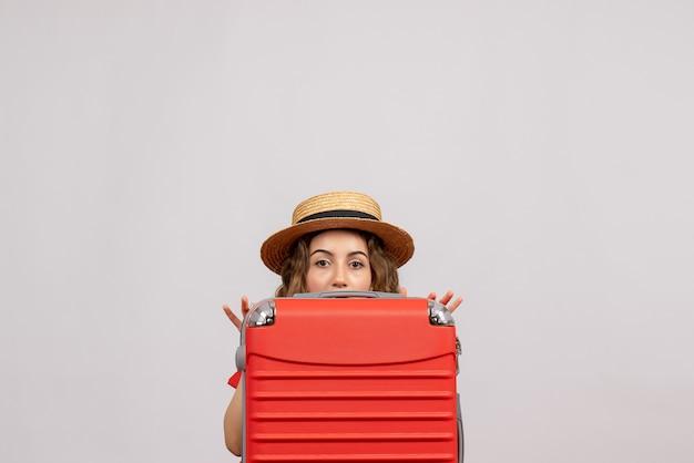 Vista frontale della giovane donna che si nasconde dietro la sua valigia