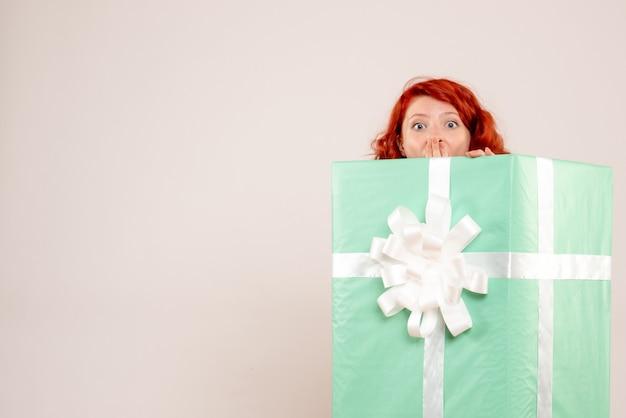 Vista frontale della giovane donna che si nasconde all'interno del regalo di natale sul muro bianco