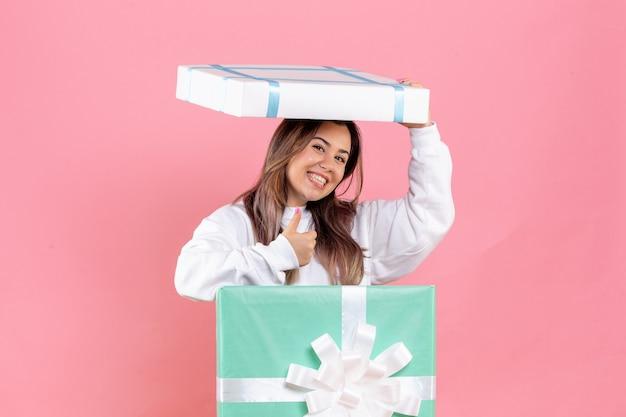 ピンクの背景に笑みを浮かべてプレゼントの中に隠れている正面図若い女性