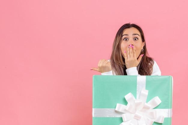 淡いピンクの背景にプレゼントの中に隠れている正面図若い女性