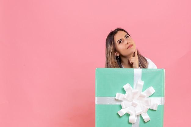 ピンクの背景にプレゼントの中に隠れている正面図若い女性