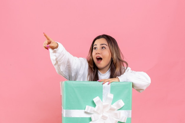 Front view young woman hiding inside present on pink floor model female photo color christmas pajama party