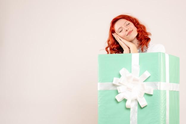 Vista frontale della giovane donna che si nasconde all'interno del presente fingendo di dormire sul muro bianco