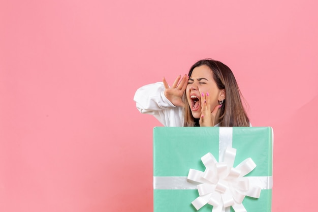 Front view young woman hiding inside present and screaming on pink background