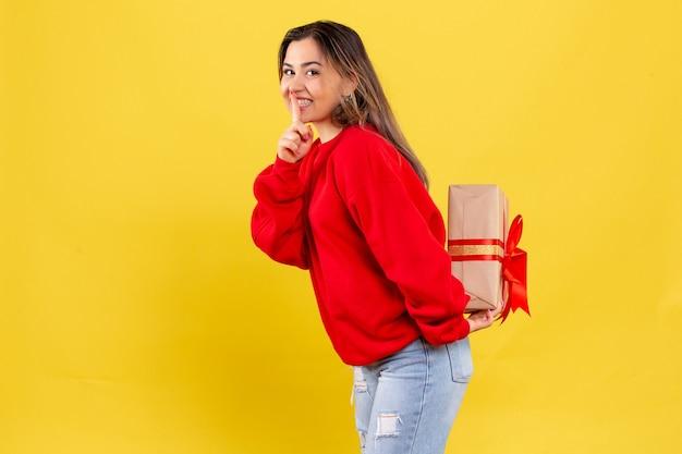 Вид спереди молодая женщина прячет рождественский подарок за спиной на желтом фоне