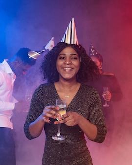 Вид спереди молодая женщина, держащая бокал шампанского