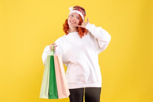Vista frontale della giovane donna che tiene i sacchetti da shopping sulla parete gialla