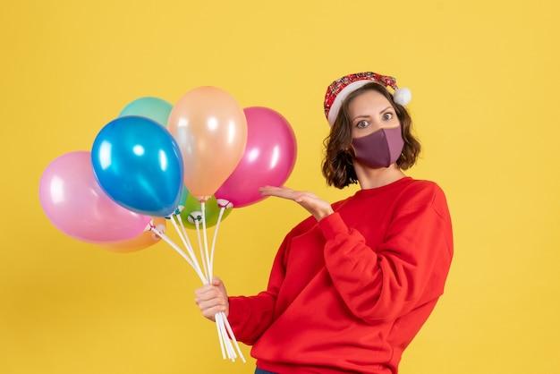 黄色のマスクで風船を保持している正面図若い女性