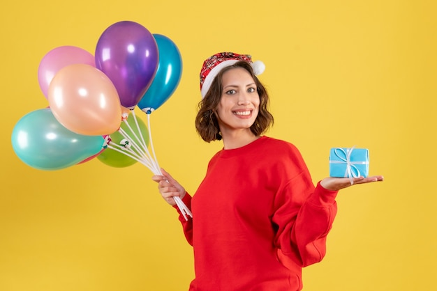 Front view young woman holding balloons and little present on yellow christmas holiday new year color woman emotion