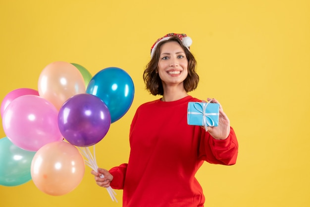 Front view young woman holding balloons and little present on yellow christmas holiday new year emotion color woman