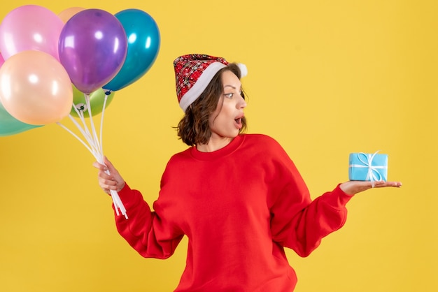 Front view young woman holding balloons and little present on yellow christmas holiday new year emotion color