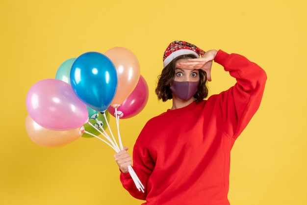 Front view young woman holding balloons in mask on the yellow party new year color celebration emotion woman