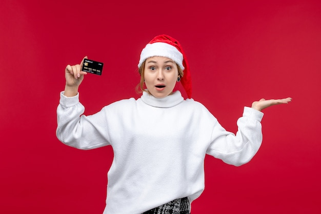 Front view young woman holding bank card on the red background