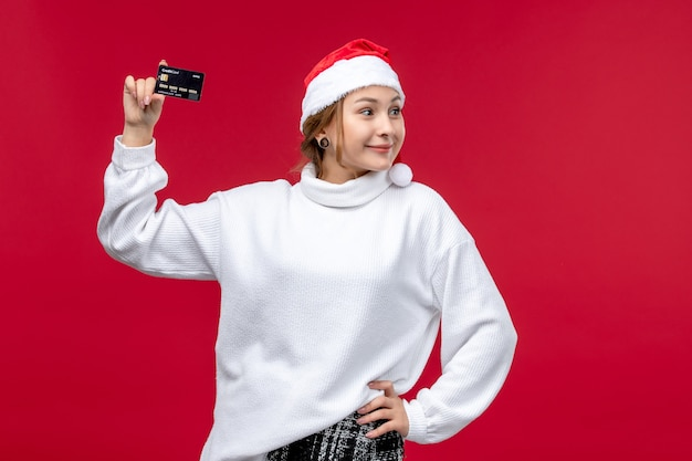 Front view young woman holding bank card on red background