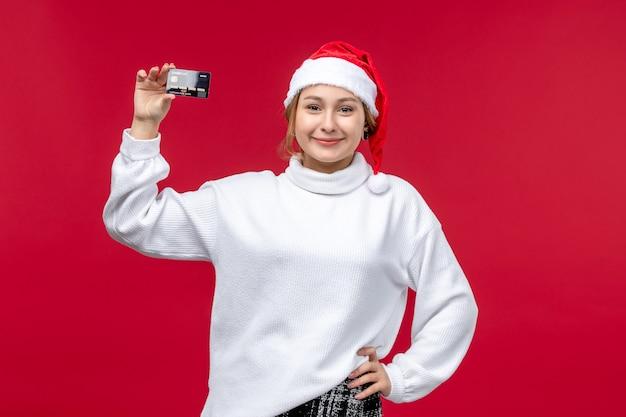 Vista frontale della giovane donna che tiene la carta di credito su sfondo rosso