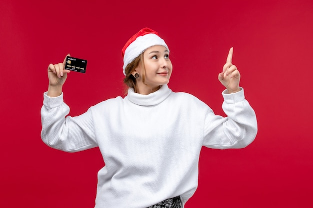 Front view young woman holding bank card on red desk