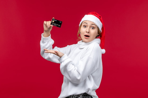 Front view young woman holding bank card on red floor red holiday money christmas