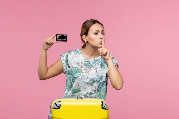 Vista frontale della giovane donna che tiene la carta di credito nera sul muro rosa chiaro