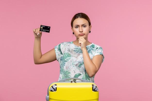 Vista frontale della giovane donna che tiene la carta di credito nera sul muro rosa