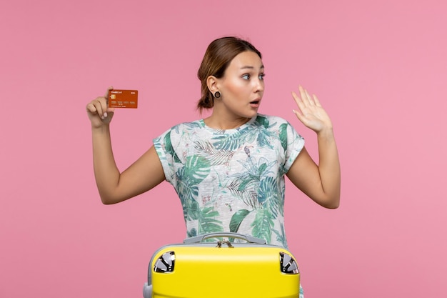Front view of young woman holding brown bank card on a pink wall