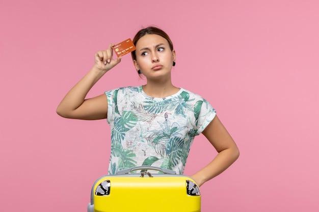 Vista frontale della giovane donna che tiene la carta di credito marrone sul muro rosa