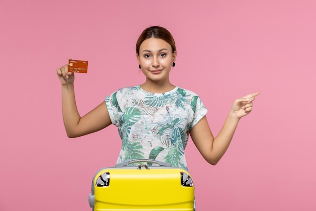 Front view of young woman holding brown bank card on the pink wall