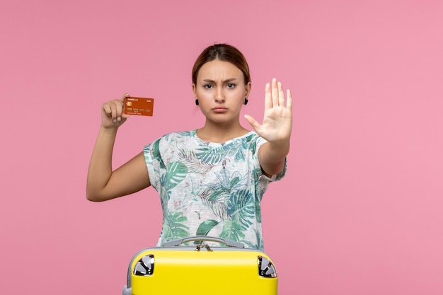 Front view of young woman holding brown bank card showing stop sign on pink wall