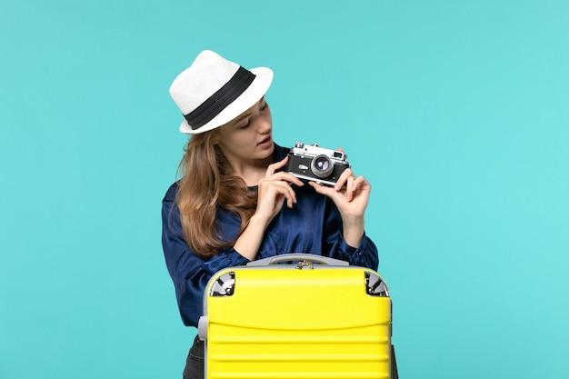 Вид спереди молодая женщина держит камеру и фотографирует на синем фоне женщина путешествие море путешествия самолет