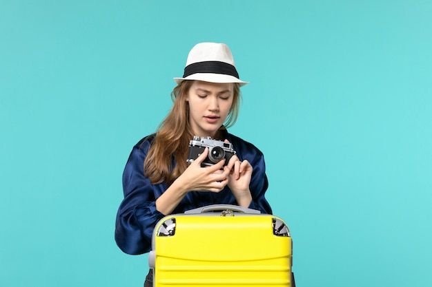 カメラを保持し、青い背景の女性の旅海の旅の航海の飛行機でそれを修正しようとしている正面図若い女性