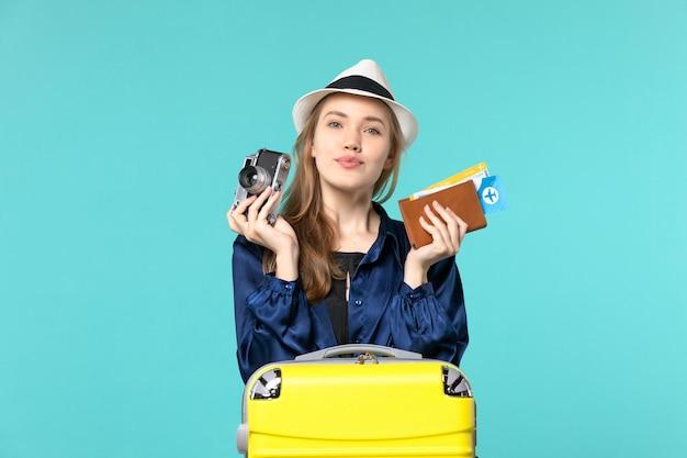 Vista frontale della giovane donna che tiene la macchina fotografica e biglietti sul viaggio aereo di viaggio di viaggio del mare del fondo blu