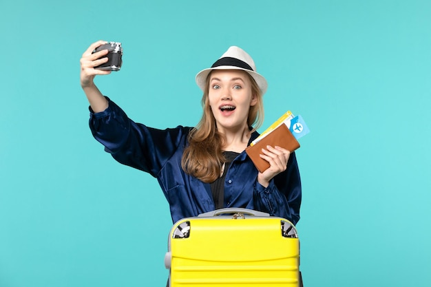 Front view young woman holding camera and tickets on blue desk sea travelling journey plane voyage