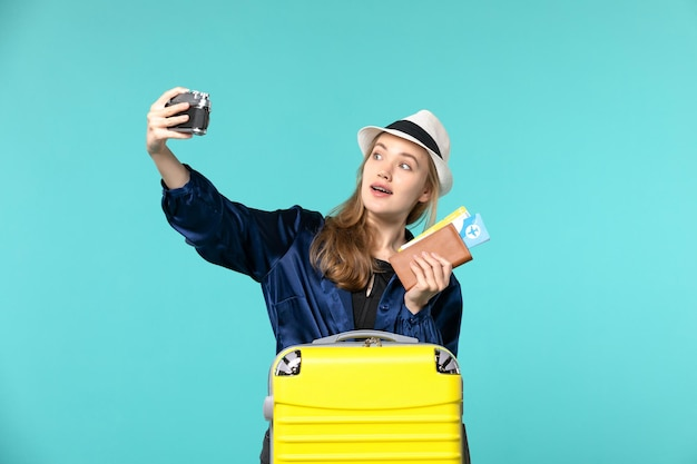 Front view young woman holding camera and tickets on light-blue background sea travelling journey plane voyage