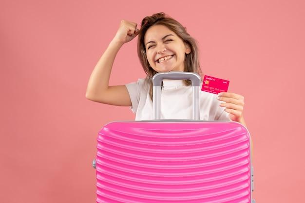 Vista frontale della giovane donna che tiene la carta dietro la valigia rosa sulla parete rosa