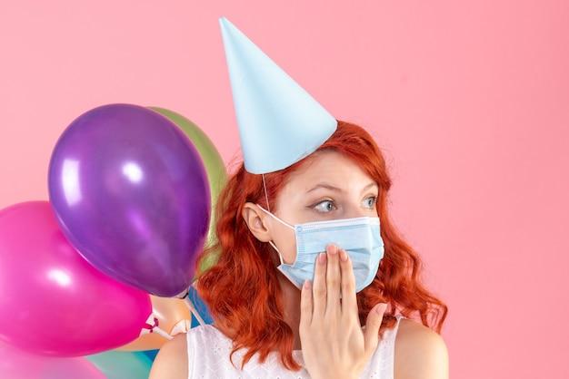 Vista frontale della giovane donna che tiene palloncini colorati sulla parete rosa