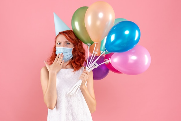 Front view of young woman holding colorful balloons in sterile mask on pink wall