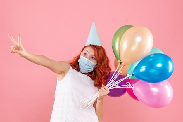 Vista frontale della giovane donna che tiene palloncini colorati in maschera sterile sulla parete rosa
