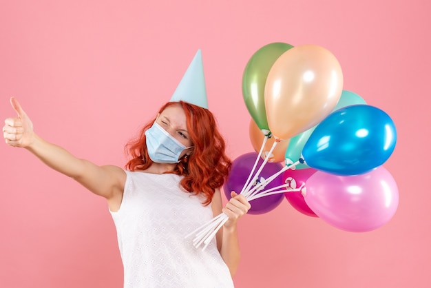 Front view of young woman holding colorful balloons in sterile mask on the pink wall