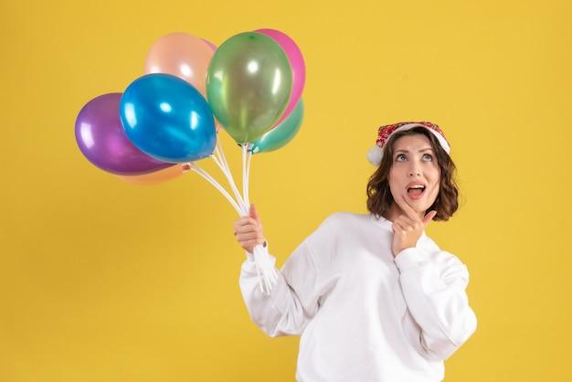 Vista frontale della giovane donna che tiene palloncini colorati sulla parete gialla