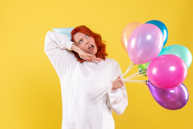 Front view of young woman holding colorful balloons on yellow wall