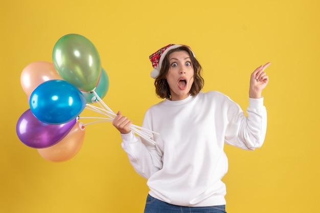 Giovane donna di vista frontale che tiene palloncini colorati su giallo