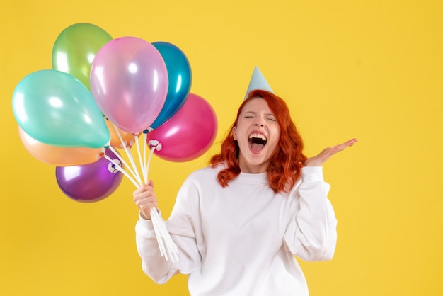 Front view of young woman holding cute colorful balloons on a yellow wall