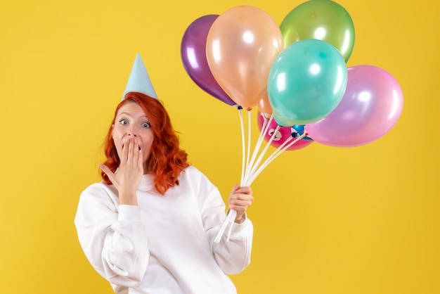 Front view of young woman holding cute colorful balloons on yellow wall