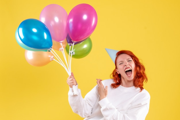Vista frontale della giovane donna che tiene palloncini colorati carino sulla parete gialla