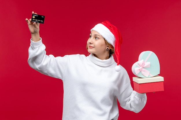 빨간색 배경에 선물 및 은행 카드를 들고 전면보기 젊은 여자