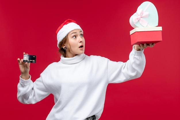 Вид спереди молодая женщина, держащая подарки и банковскую карту на красном фоне