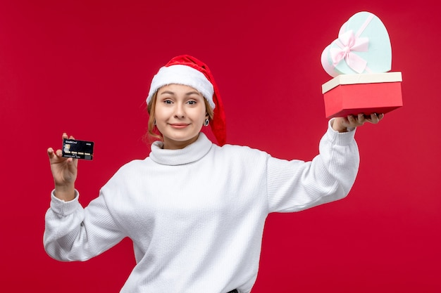 Front view young woman holding gifts and bank card on a red background
